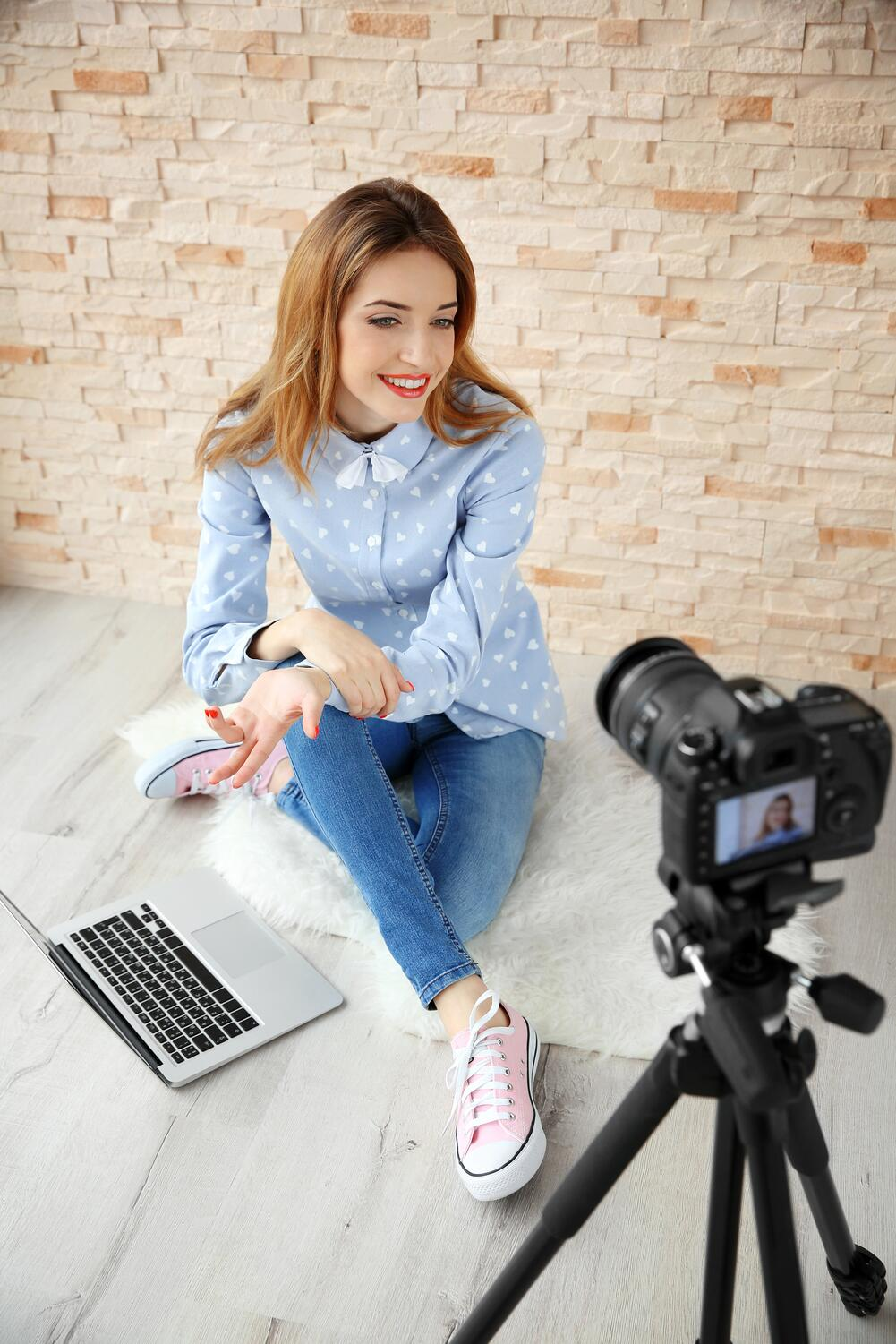 stock-photo-young-female-blogger-with-laptop-recording-video-at-home-435955549.jpg